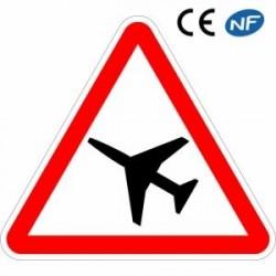 Panneau de signalisation annonçant la traversée d'uneaire dedanger aérien (A23)